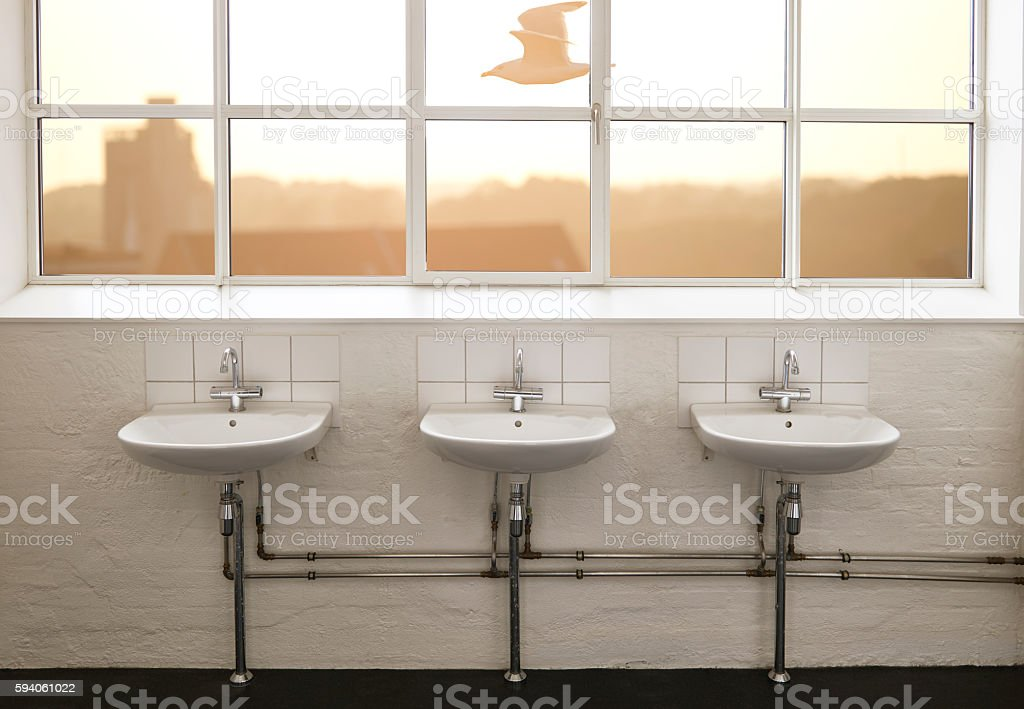Retro styled sparse bathroom with sinks stock photo