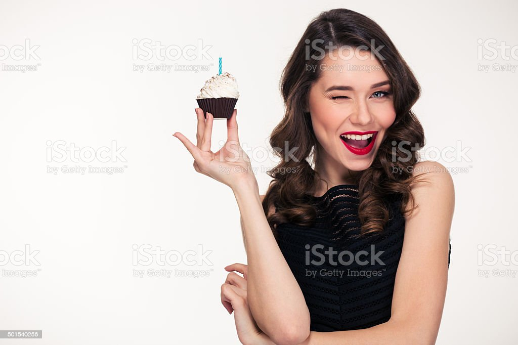 Retro styled woman holding birthday cupcake with candle and winking stock photo