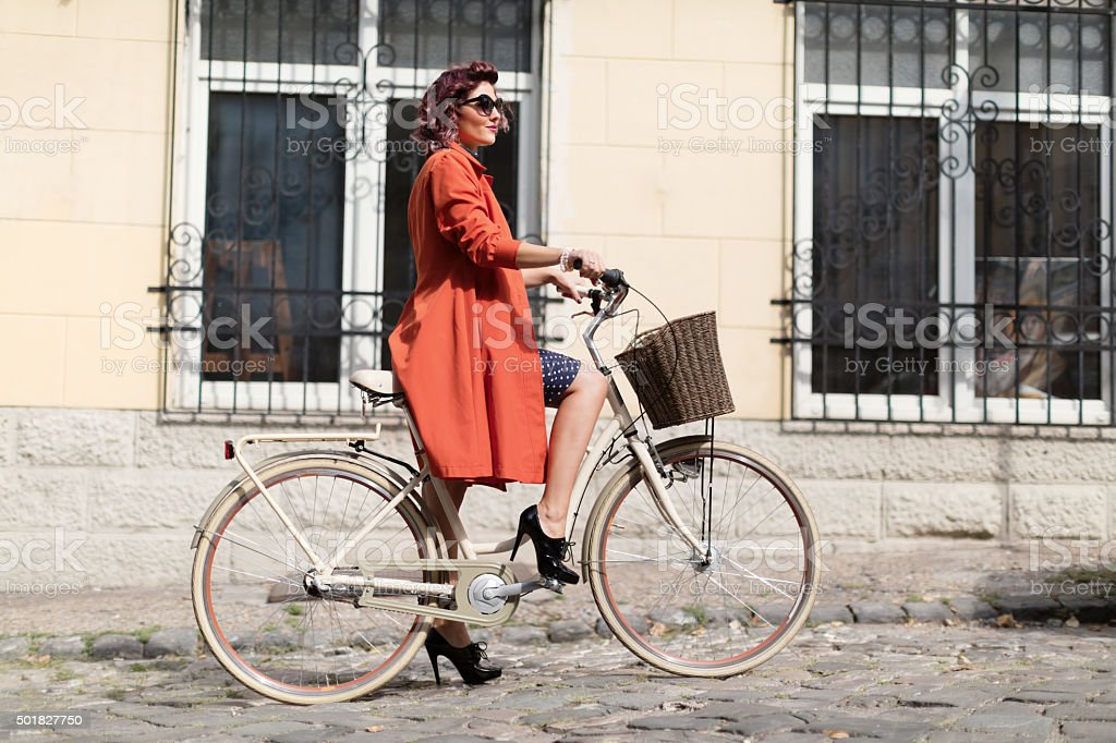 Retro styled woman riding a bike stock photo
