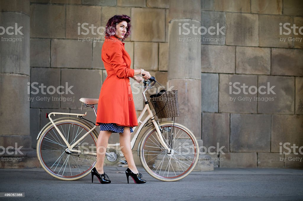 Retro styled woman with bike stock photo