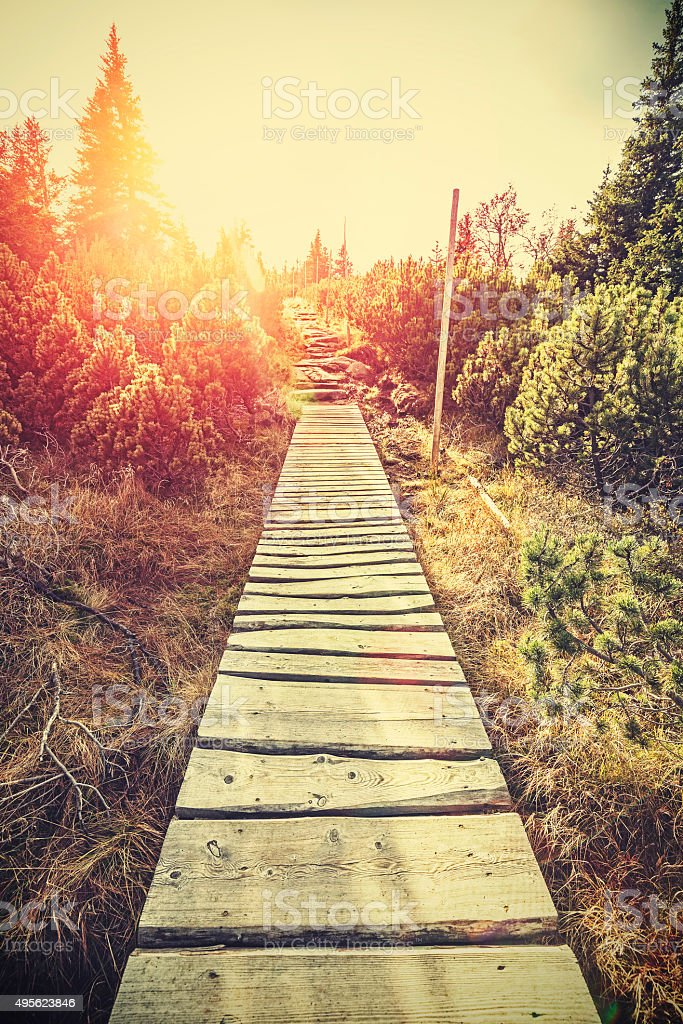 Retro stylized mountain wooden path in mountains at sunset. stock photo