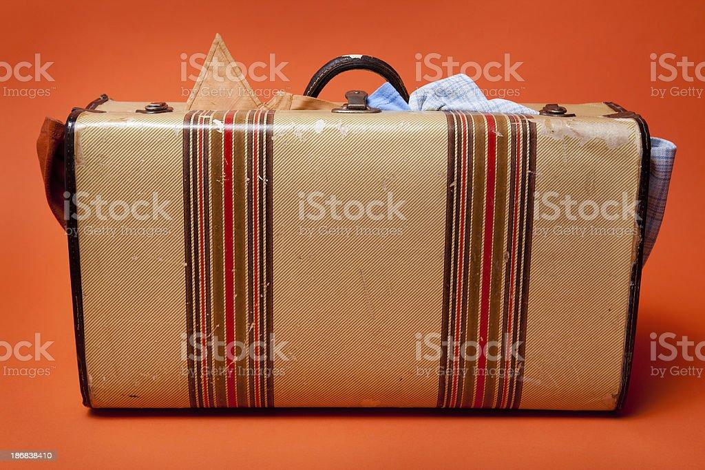 Retro Suitcase Overstuffed with Clothing on Orange Background royalty-free stock photo