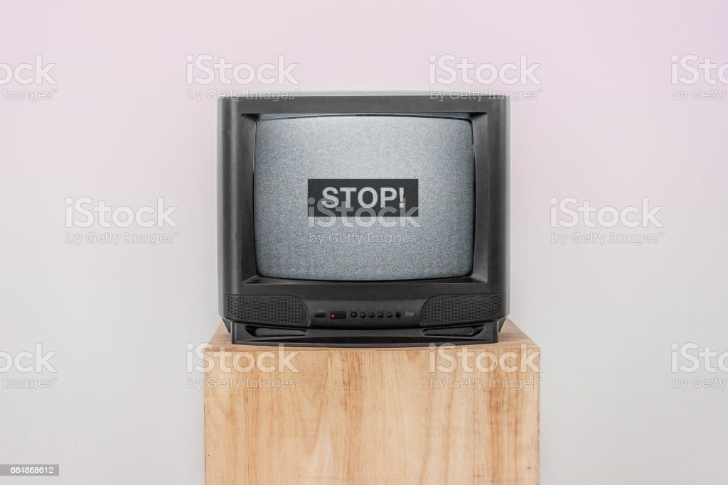 Retro Television with screen noise and Stop word on a wooden shelf stock photo