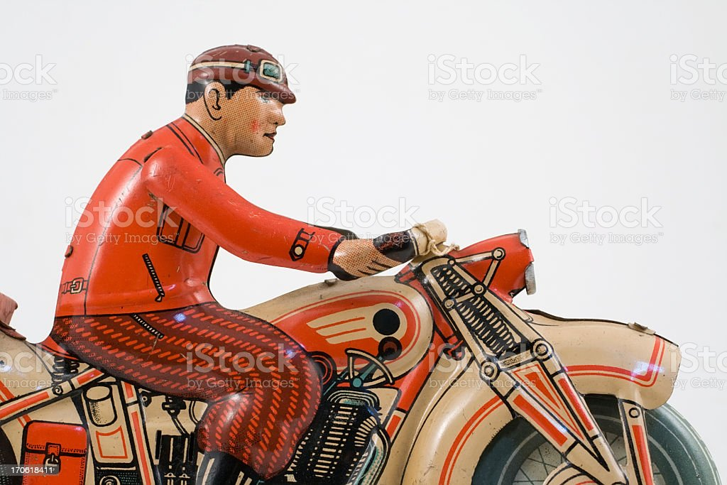 Retro tin toy motorcycle  rider dressed in red jacket. stock photo