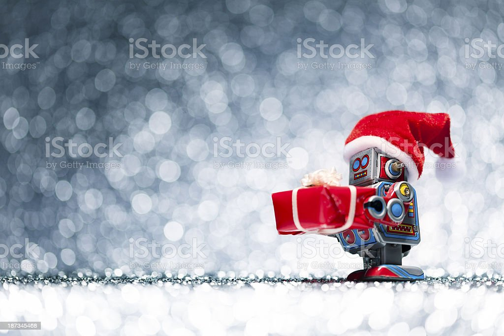 Retro tin toy santa robot holding christmas present stock photo
