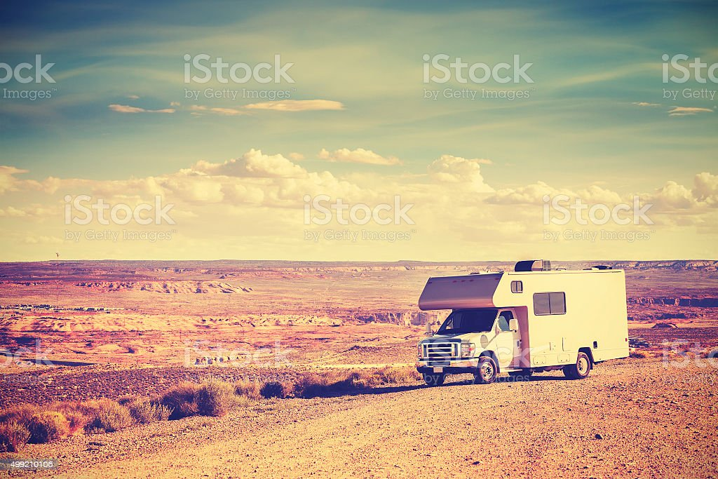 Retro toned camper parked by canyon, vacation concept. stock photo