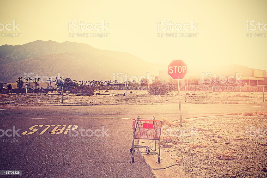 Retro toned empty shopping trolley left on street at sunset. stock photo