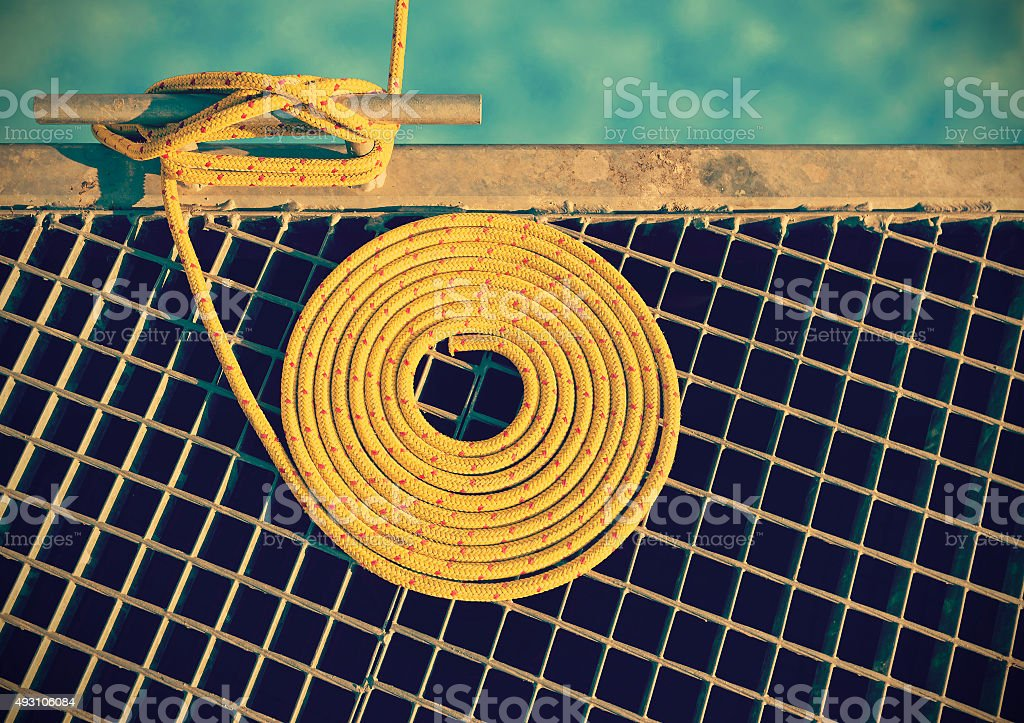 Retro toned marine background made of mooring rope on pier. stock photo