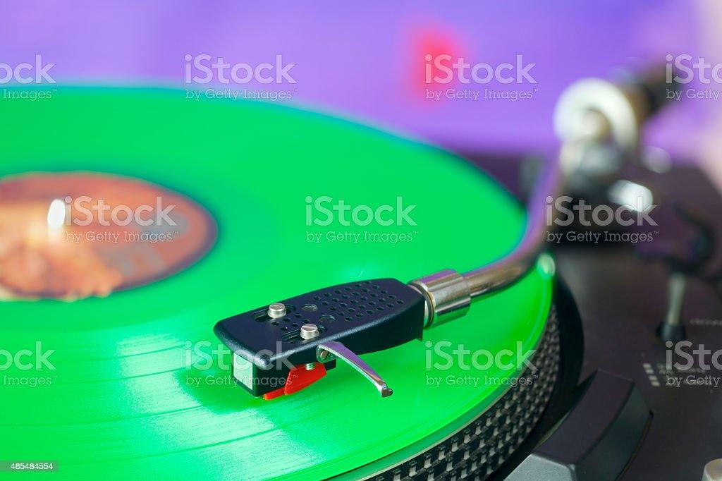 Retro turntable with green vinyl record, stock photo