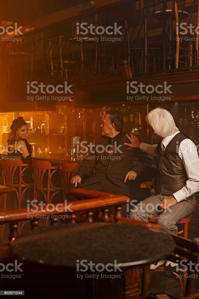 Retro  Two old fashioned senior man  and  woman  in pub stock photo