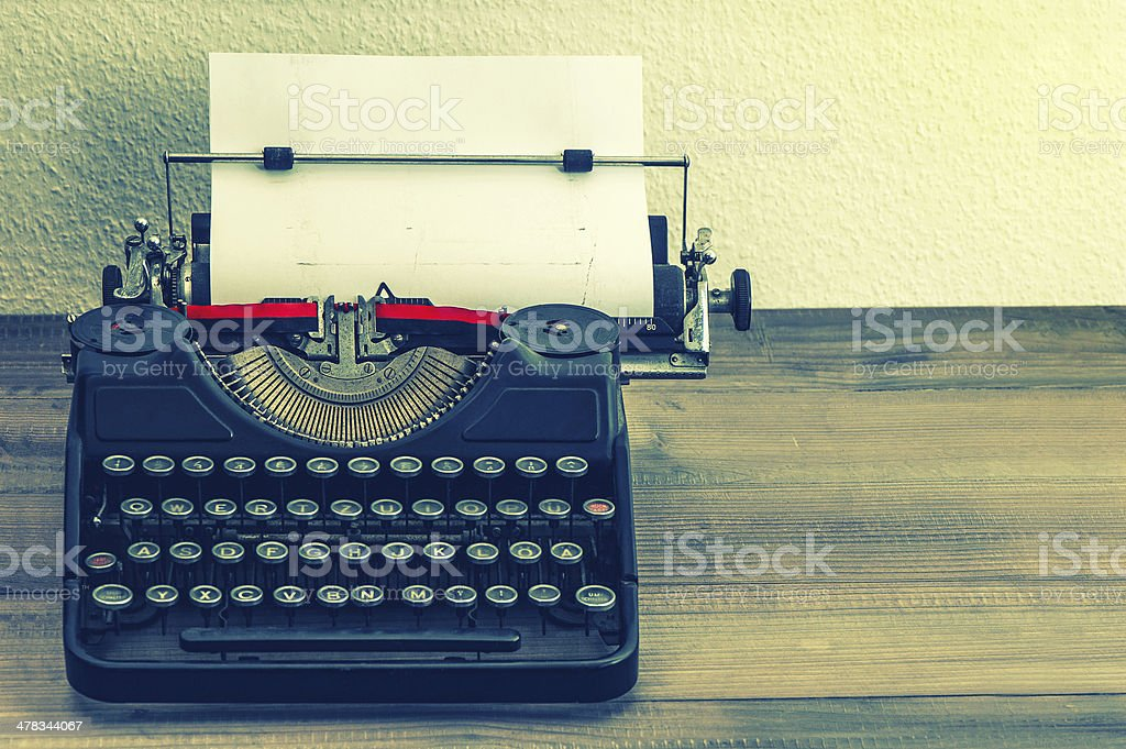 retro typewriter with white paper page. vintage style stock photo