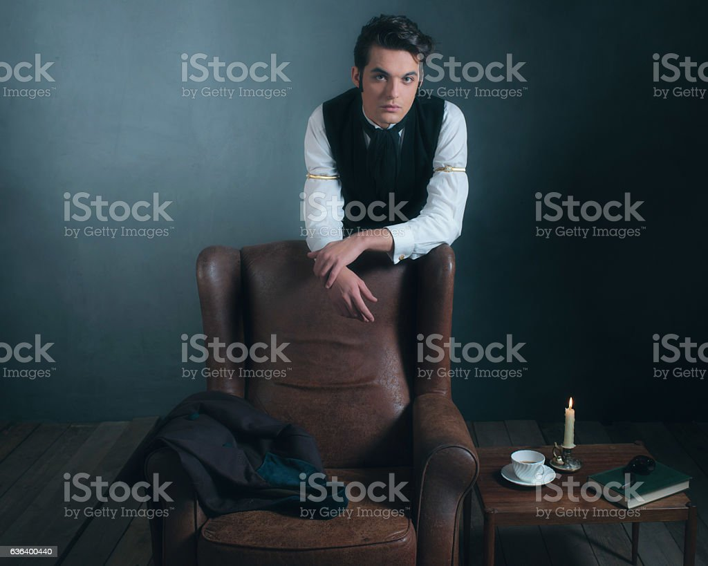 Retro victorian man leaning on back of leather chair. stock photo