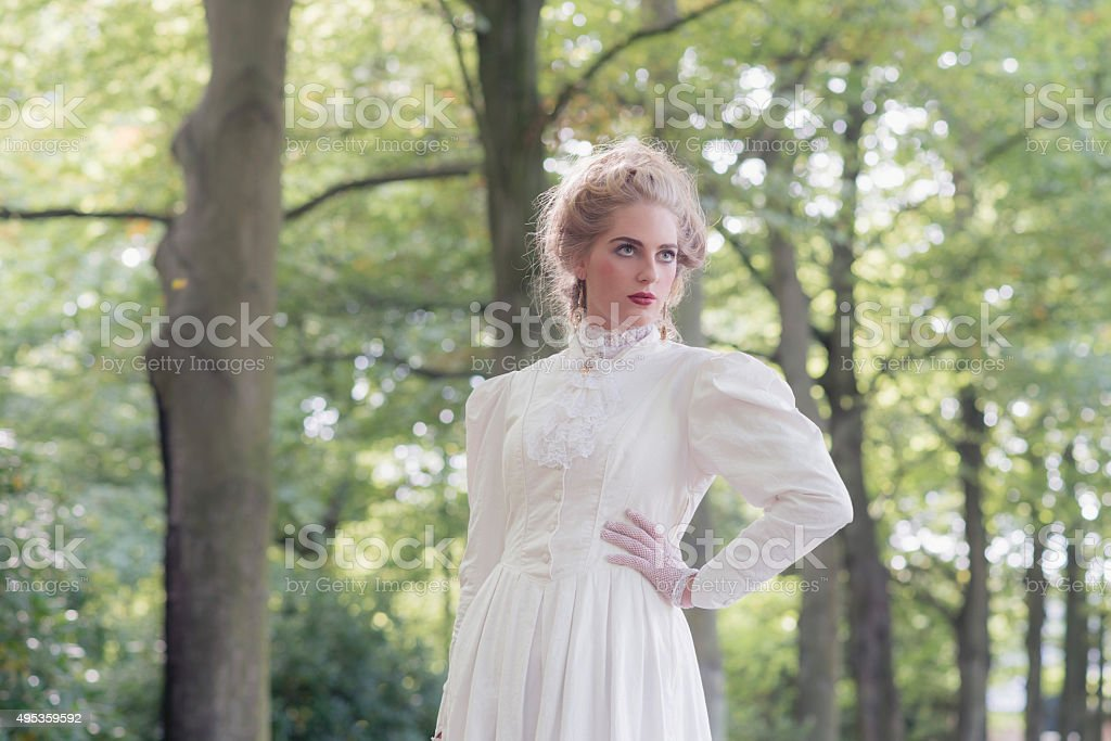 Retro victorian woman in front of tree row. stock photo