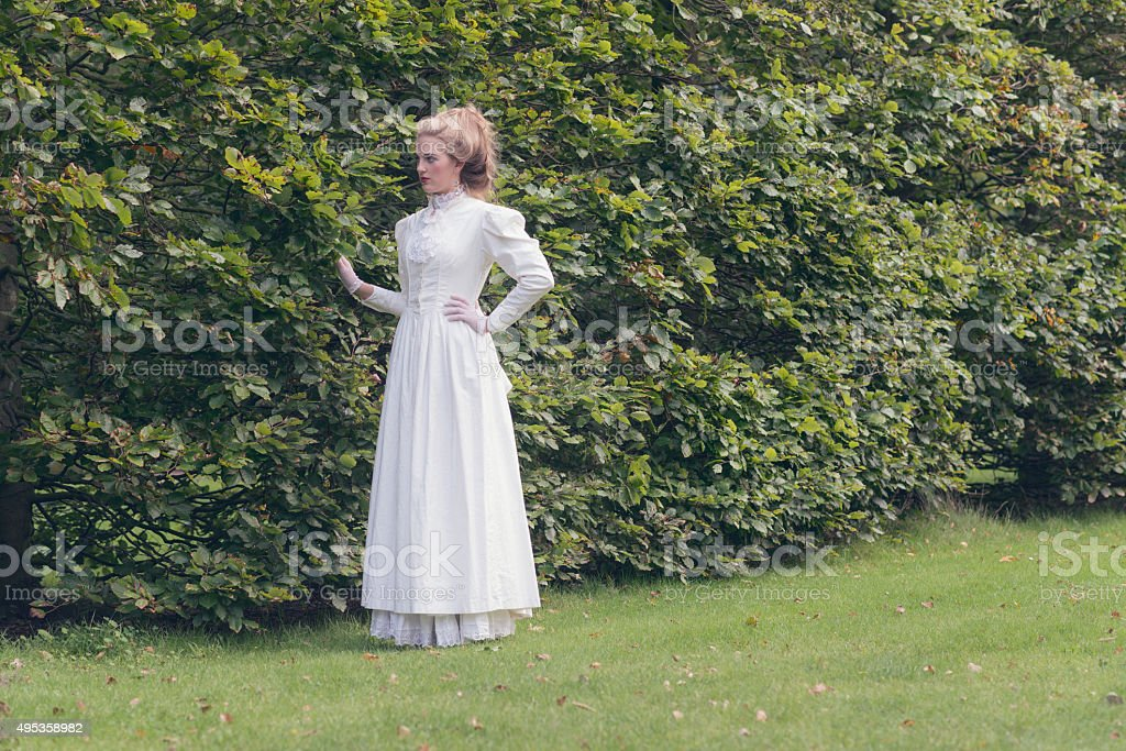 Retro victorian woman walking in garden touching tall hedge. stock photo