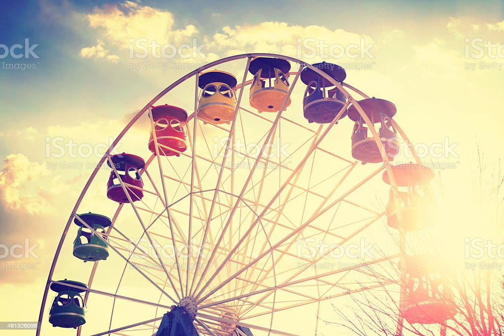 Retro vintage stylized picture of ferris wheel at sunset. stock photo