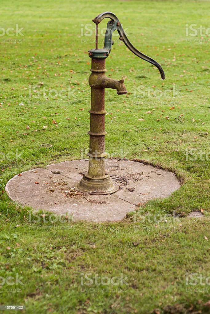 Retro water pump on grass royalty-free stock photo