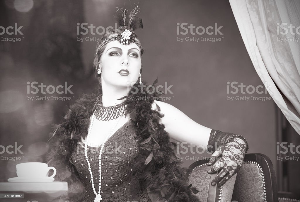Retro Woman 1920s - 1930s Sitting with Cup of Tea royalty-free stock photo