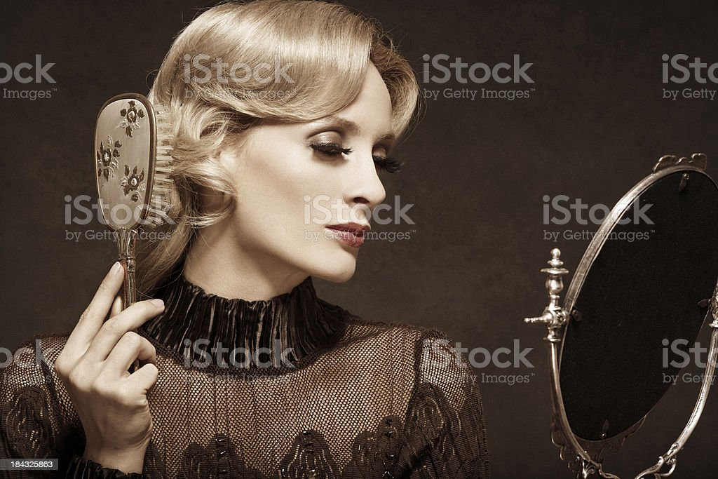 Retro woman combing her hair with hairbrush royalty-free stock photo