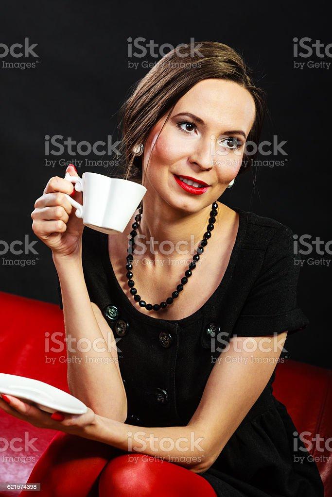 Retro woman holds tea cup sitting on sofa stock photo
