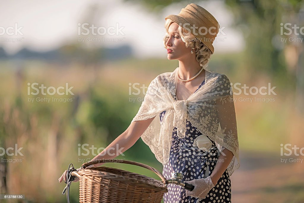 Retro woman in 1930s fashion with bicycle in rural landscape. stock photo