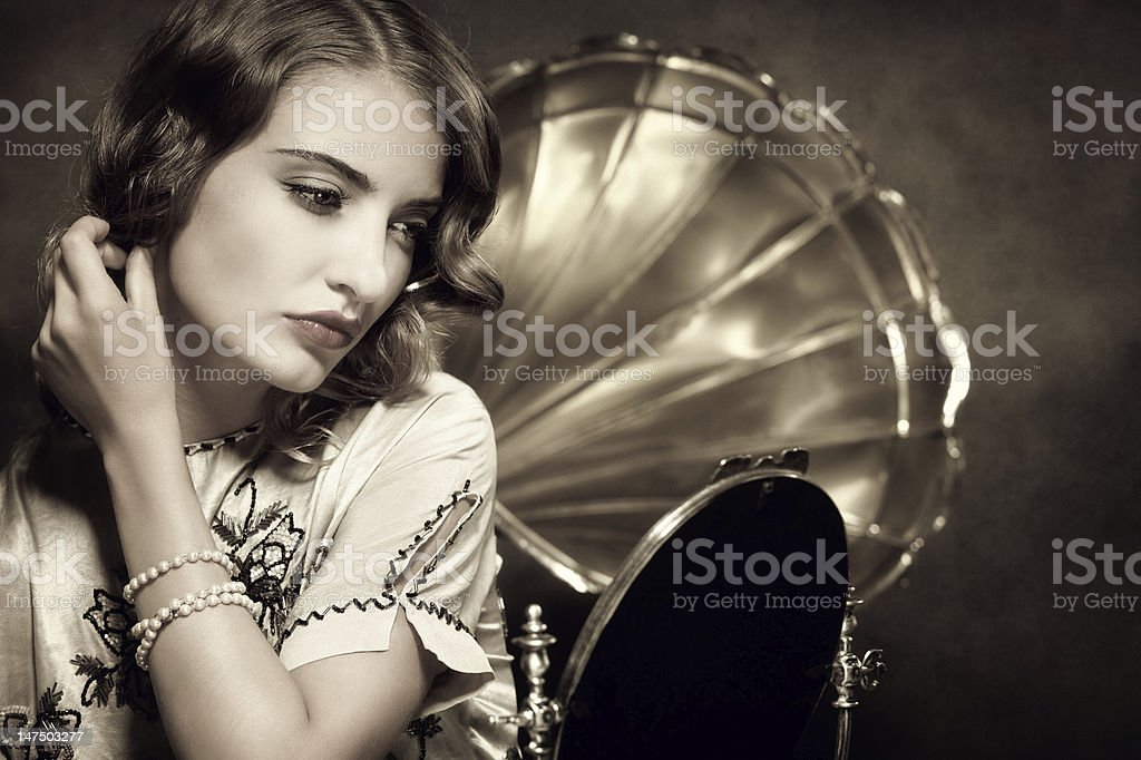 retro woman listening to music and looking in the mirror stock photo