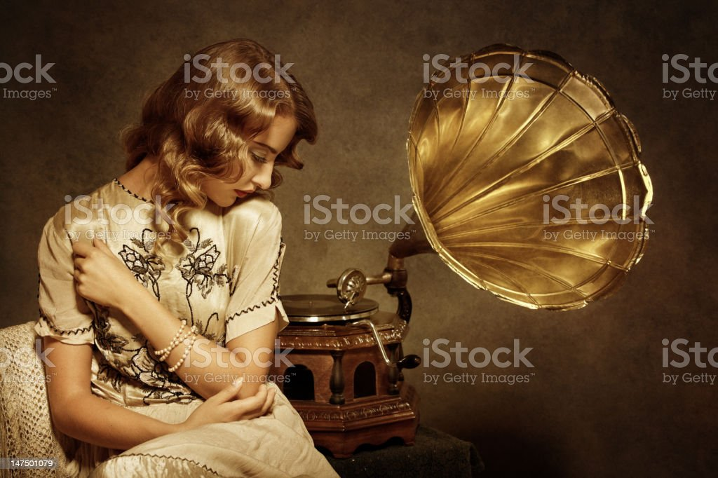 Retro woman listening to music on gramophone royalty-free stock photo