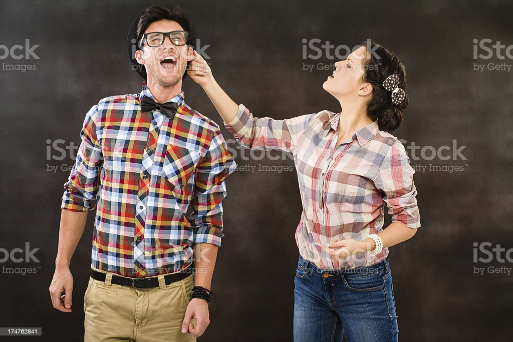 Retro woman pulling her boyfriends ear stock photo