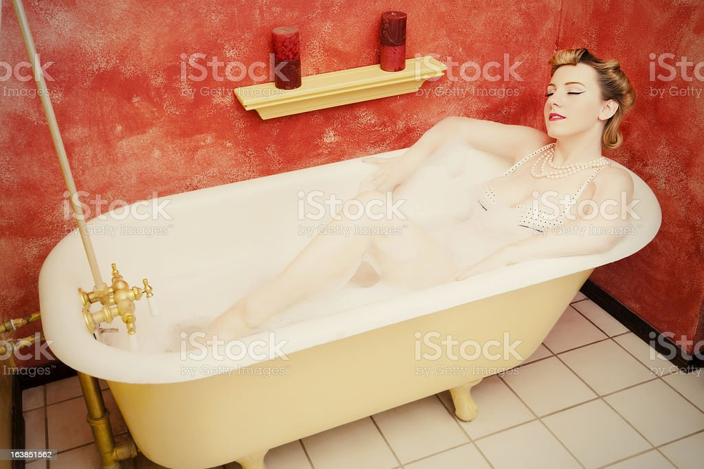 Retro woman relaxing in an old-fashioned bathtub - pinup style stock photo