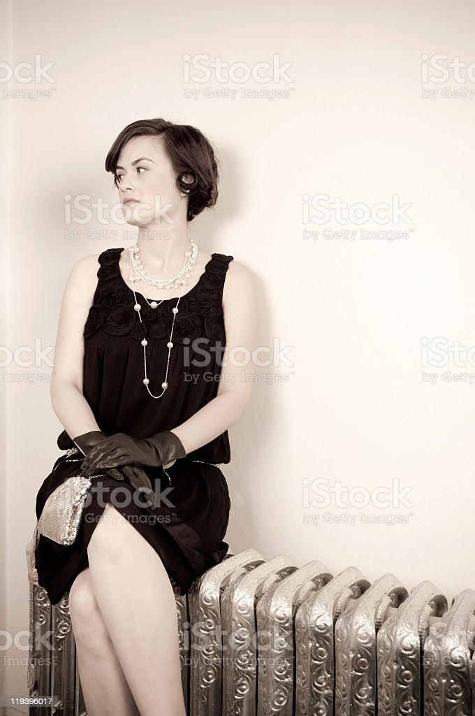 Retro woman sitting on antique heater looking away stock photo