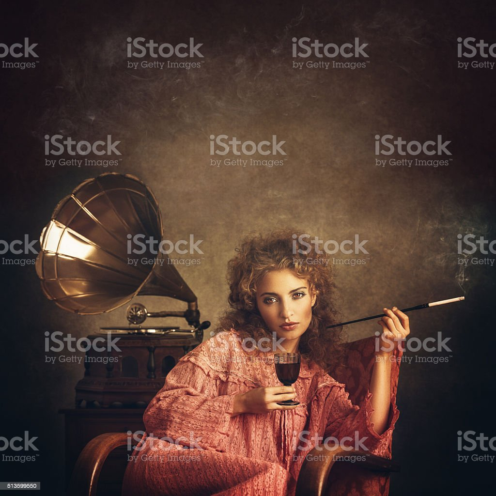 Retro woman smoking and drinking at the gramophone stock photo