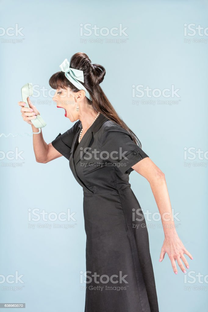 Retro Woman yelling into Phone Receiver stock photo