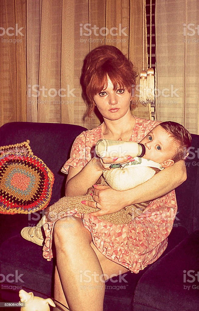 Retro young mother feeding her cute son stock photo