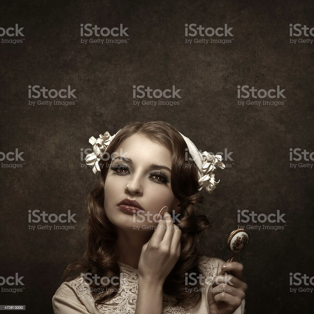 retro young woman applying make-up stock photo