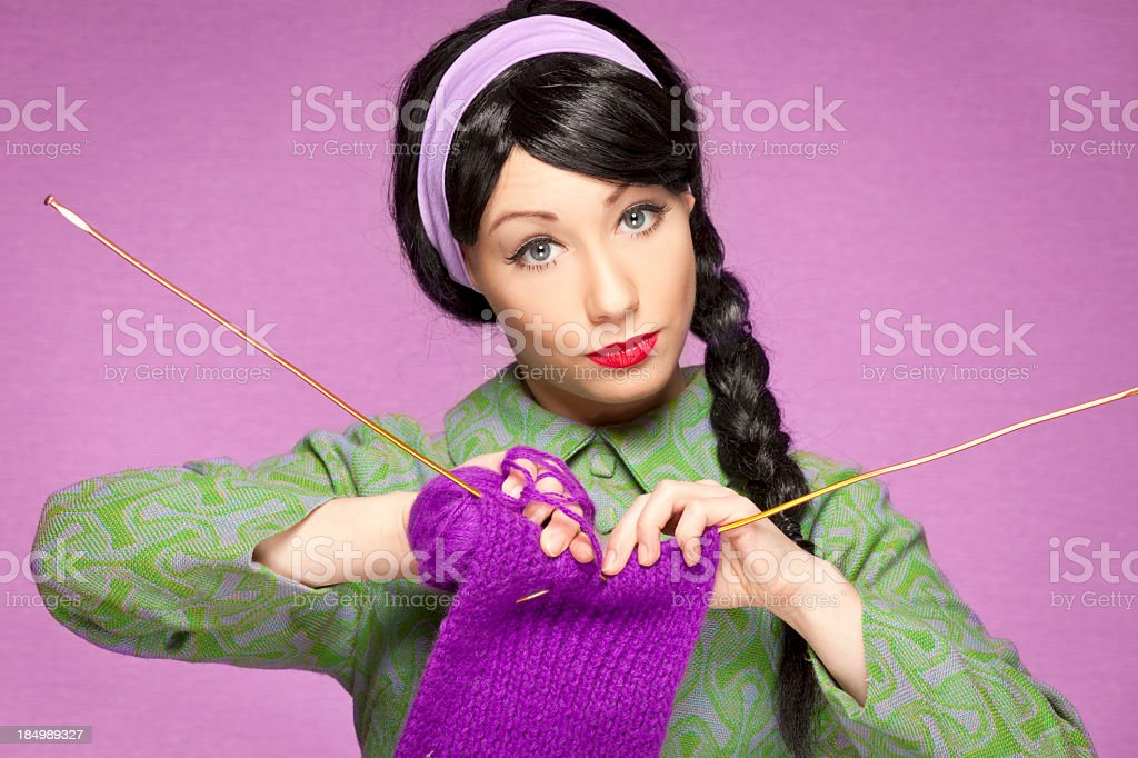 Retro-style woman wearing green, knitting with purple yarn royalty-free stock photo