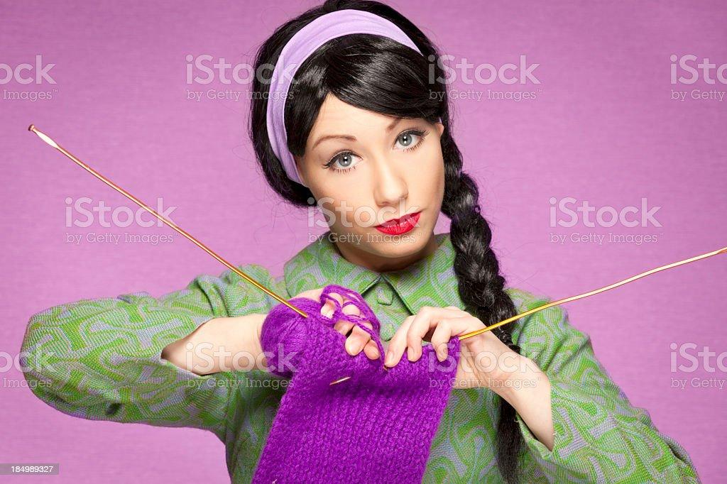 Retro-style woman wearing green, knitting with purple yarn stock photo
