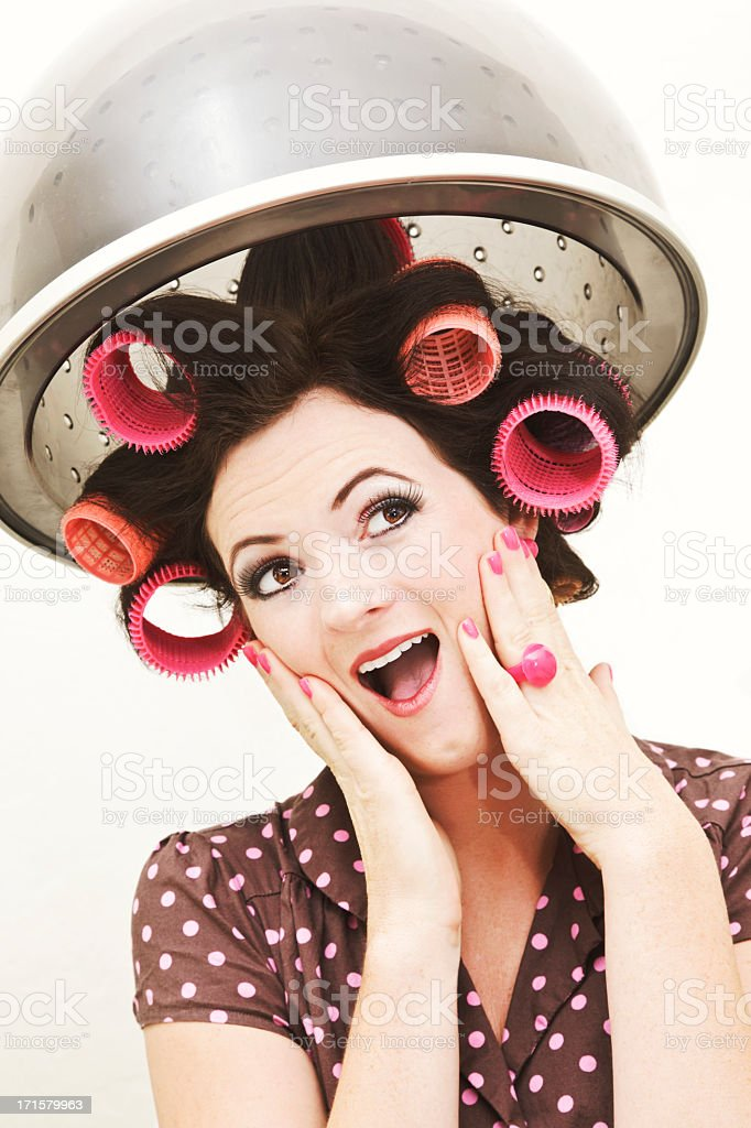 Retro-styled young woman in curlers under salon hairdryer stock photo