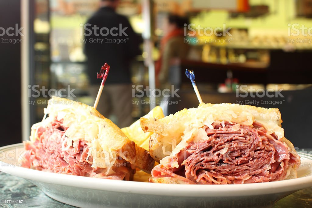 A Reuben sandwich on a white plate in a restaurant stock photo