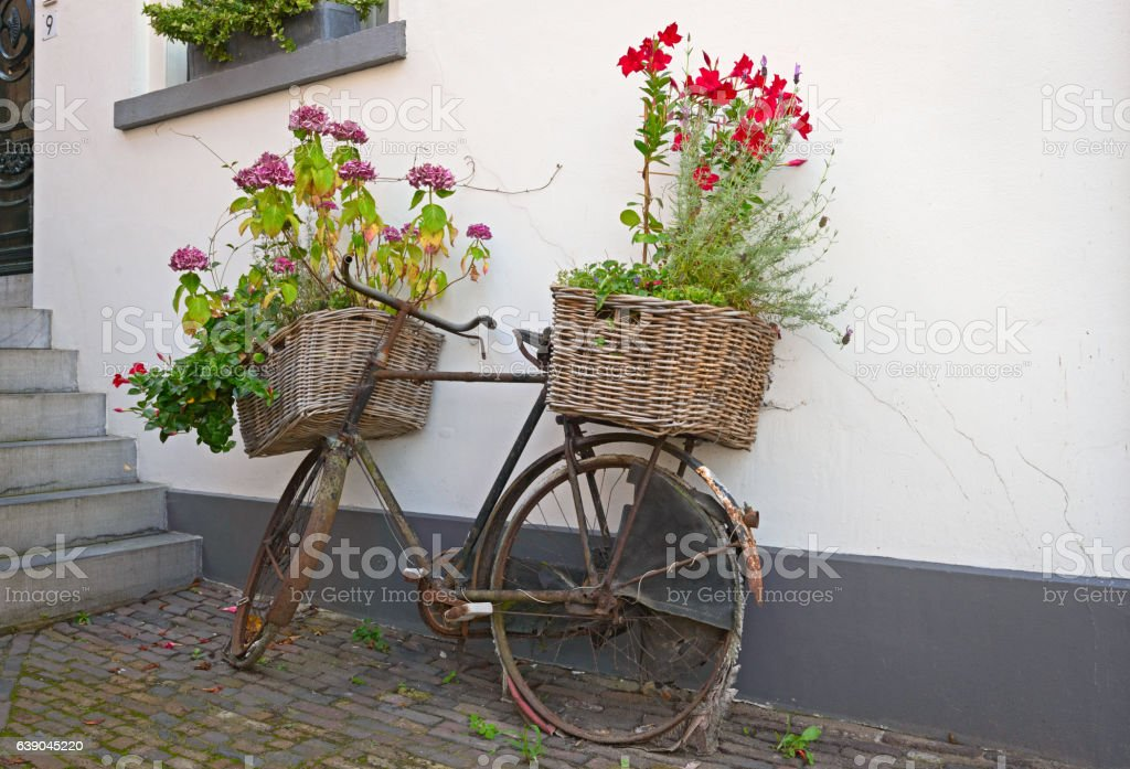 Reused bycycle with baskets of flowers stock photo