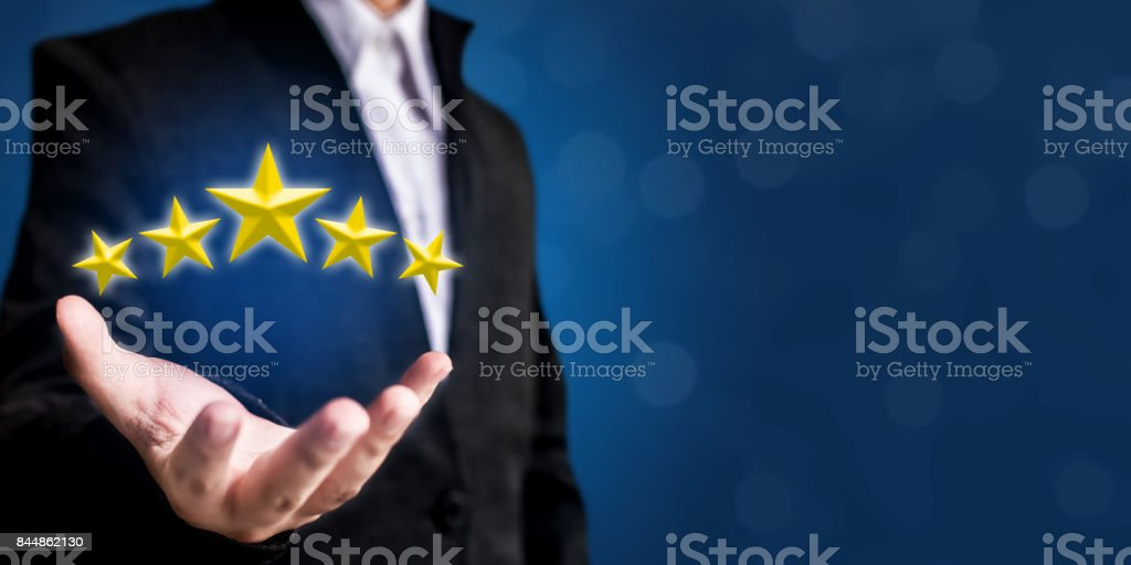 Review, increase rating or ranking, evaluation and classification concept. Businessman hand holding yellow five stars stock photo