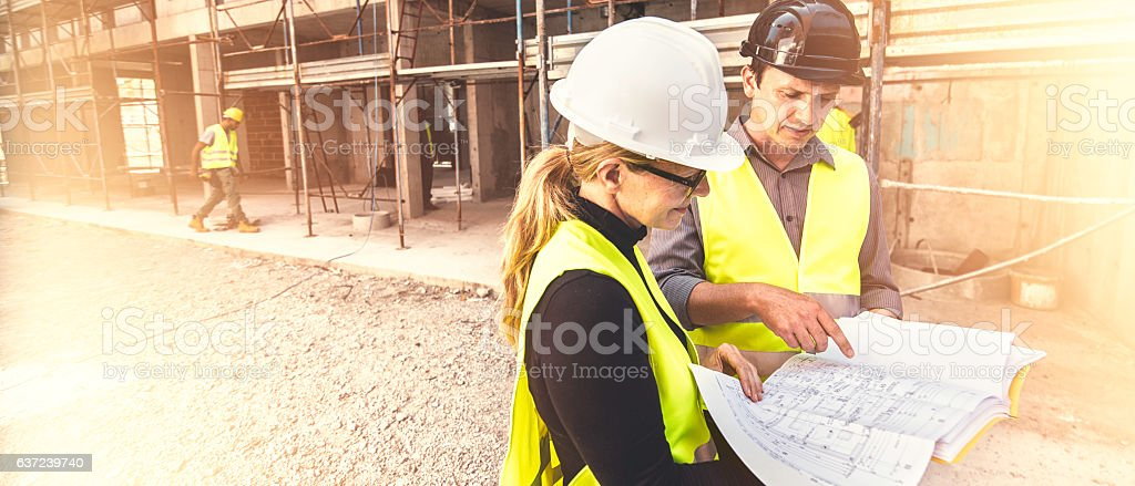 Reviewing blueprints on a construction site stock photo