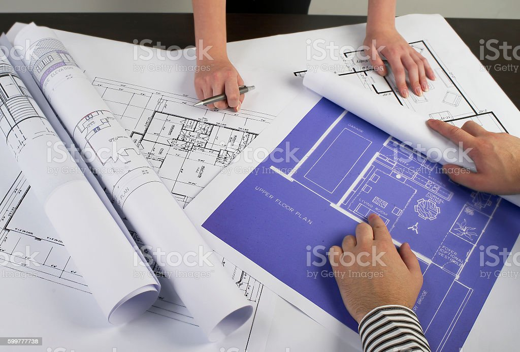 Reviewing the blueprints on desk stock photo