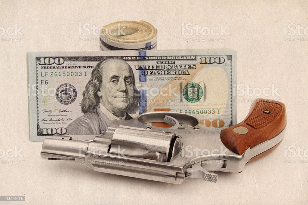 Revolver and roll of US currency stock photo