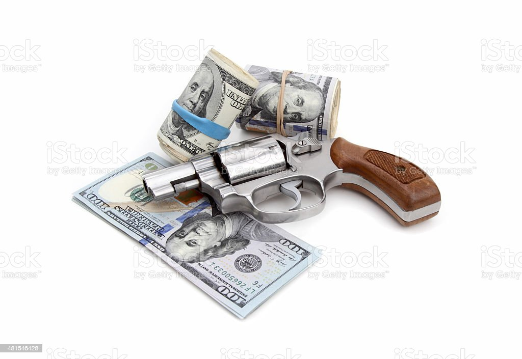 Revolver and rolls of US currency stock photo