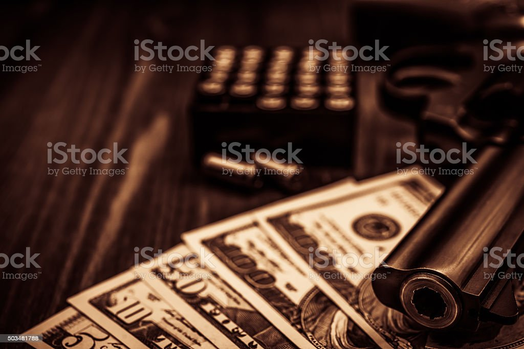 Revolver with a bundle of money stock photo