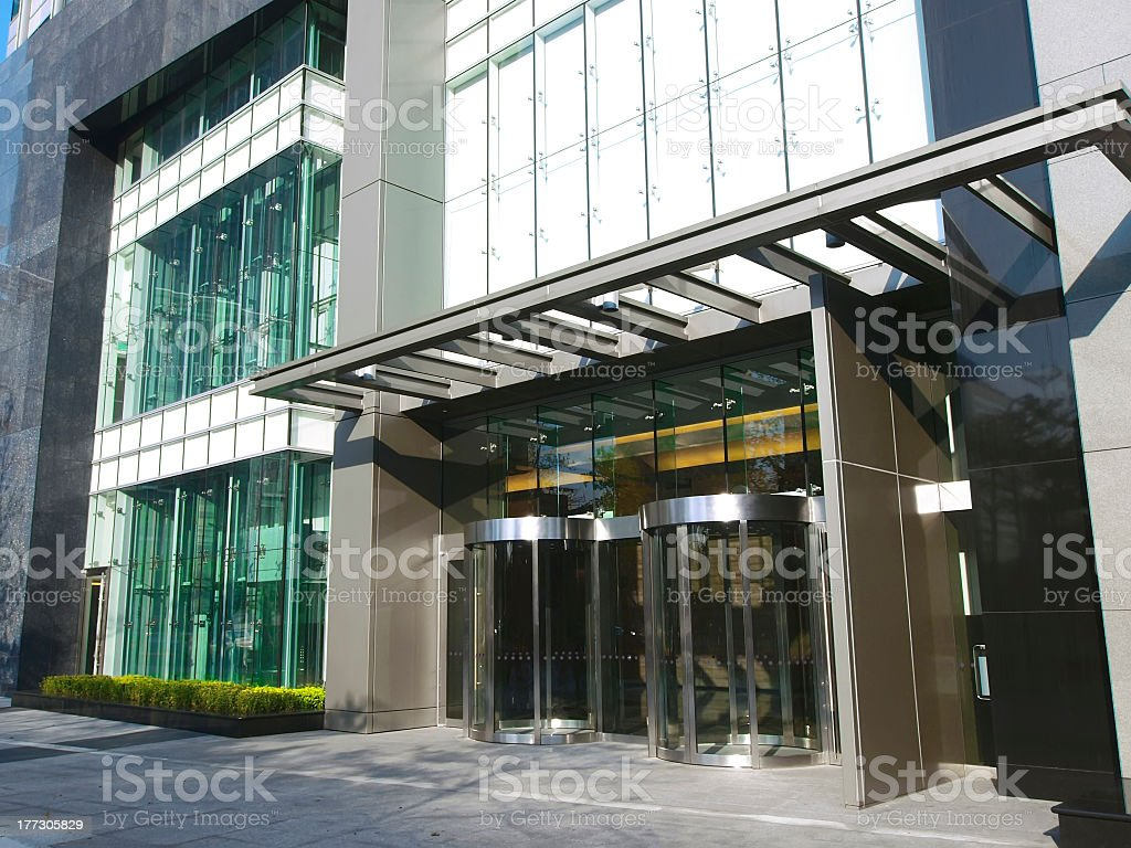 2 revolving glass doors in glass fronted modern building stock photo