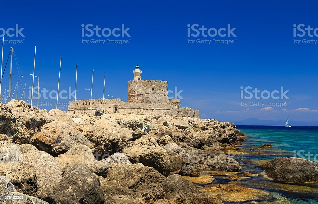 Rhodes harbor with old fort in background  stones in foreground stock photo