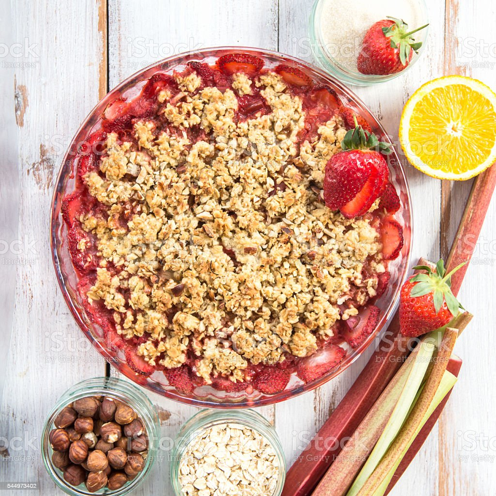 Rhubarb and Strawberry crumble with all ingredients nearby stock photo