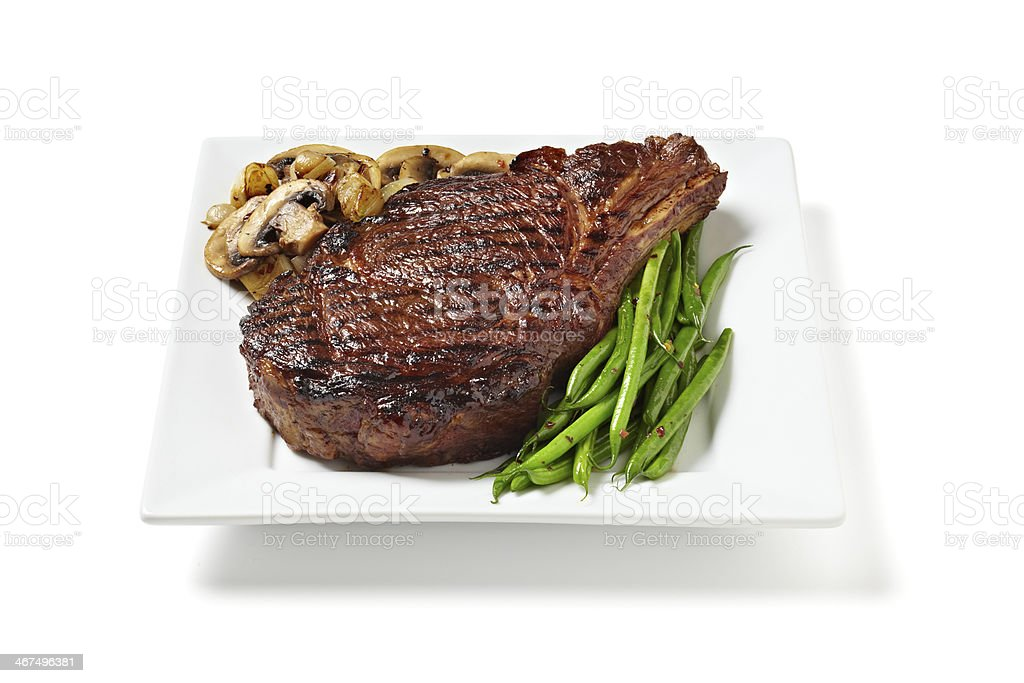 A rib eye steak served between mushrooms and green beans stock photo