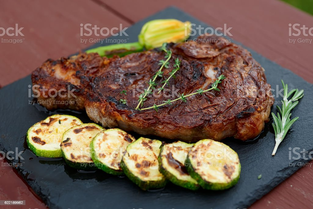 Rib eye steak with vegetables on a slate plate stock photo