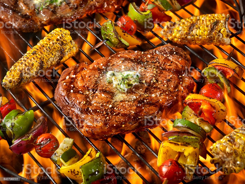 BBQ Rib Eye Steaks with Herb Butter,corn and Kabobs stock photo